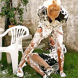 Two hot babes playing together in messy white stuff outdoors