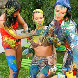 Sexy chicks paint on each other on a park bench topless
