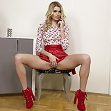 Karina Grand posing in flowered blouse and short red skirt