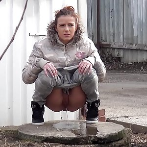 Sexy brunette pissing on an industrial estate